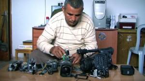 Film maker Emad Burnat with his broken cameras