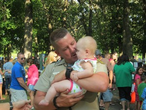 Officer Chris Flatness snuggles a baby in East Park during 2013 National Night Out event