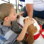 Jacob Howard, age 4, gives and receives kisses from most of the dogs