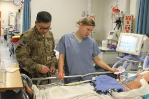 Lt. Lyndon Guo, left, and Lt. j.g. Kathleen Stopyra, both critical care nurses at the Multinational Medical Unit, a hospital at Kandahar Airfield, Afghanistan, conduct a change of shift to take care of an Afghan child who was wounded in a rocket attack on Saturday, Jan. 18, 2014, in Maiwand district. (U.S. Army photo by Sgt. Antony S. Lee)