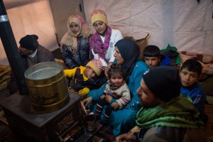 Members of a Syrian refugee family huddle around a stove inside their shelter days ago in Lebanon's Bekaa Valley. Photo: UNHCR/A. McConnell Members of a Syrian refugee family huddle around a stove inside their shelter days ago in Lebanon's Bekaa Valley. Photo: UNHCR/A. McConnell