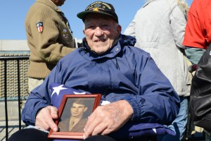Army veteran Hugh Phelps holds a picture of his brother Patrick, an Army veteran, on his lap atop a folded American flag, as he visited the World War II Memorial in Washington, D.C., April 5, 2014. Phelps, of Ellicott City, Md., visited the memorial with the Honor Flight Capital Region.