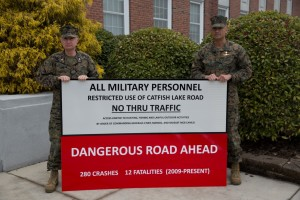 MARINE CORPS BASE CAMP LEJEUNE, N.C. - Col. James W. Clark, deputy commander of Marine Corps Installations East, and Sgt. Maj. Ernest K. Hoopii, Marine Corps Installations East sergeant major, display the new Catfish Lake Road warning sign aboard Marine Corps Base Camp Lejeune, March 6. It was deemed off-limits to base personnel due to the dangerous driving conditions.