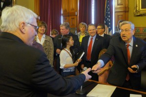 Senator Schoenjahn takes a pen from Governor Terry Branstad during the signing  of a bill on dyslexia earlier this month