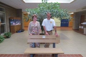 Allison Stevenson, Roosevelt Elementary School principal, and Todd Von Ehwegen, Co-Chair of the Mason City Earth Day Committee, with a recycled plastic bench won by Roosevelt in a milk jug collecting contest for the annual Earth Day Event.