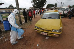 A health care worker disinfecting a taxi in Liberia at an Ebola treatment centre. Photo: WHO/R. Sørensen