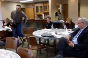 Seconds later, Tim Ackerman, working for the Globe Gazette, advances across the room and makes contact with Marquardt