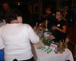 """Cassie Peterson of Hy-Vee offers """"Lakewater"""" in the Signature Cocktail Competition held at the Surf Thursday evening"""