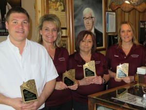Stars of Hospitality Award Winners Matthew Rumeliote, Pam Bartholomew, Cindy Papouchis and Donna Meacham received the Iowa Restaurant Association's Stars of Hospitality Award. Each has worked at least 20 years at Northwestern Steakhouse in Mason City. They are standing in front of a painting of restaurant founder Tony Papouchis who opened and operated the award-winning restaurant for more than half a century. Northwestern Steakhouse is now owned and operated by Tony's son and his wife, Bill and Ann Papouchis.