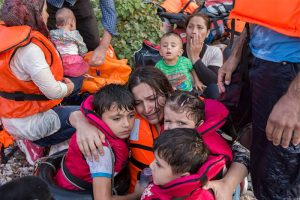 A Syrian mother cries with relief as she embraces her three young children after a rough sea crossing. UNHCR/Ivor Prickett