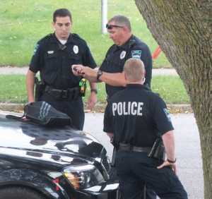 Police officers photograph a black backpack for evidence